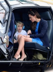 Duke of Cambridge and Prince George sit in a Squirrel helicopter during a visit to the Royal International Air Tattoo at RAF